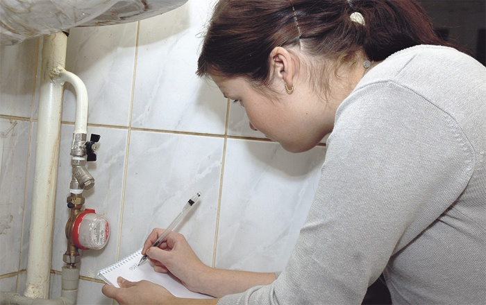 Девушка снимает показания счетчика