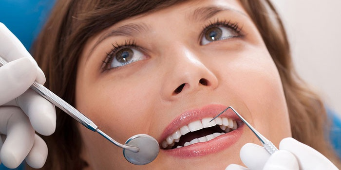 Стоматолог проверяет зубы пациентки