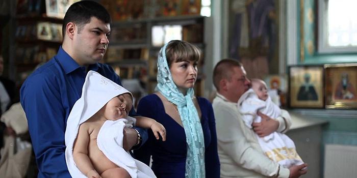 Крестные держат детей на руках