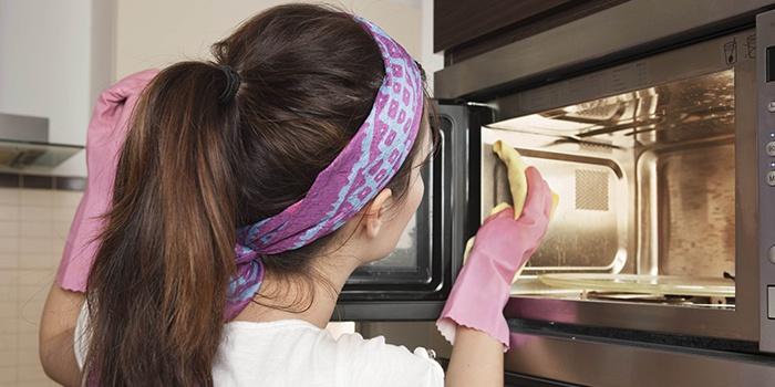 Девушка чистит микроволновку от жира