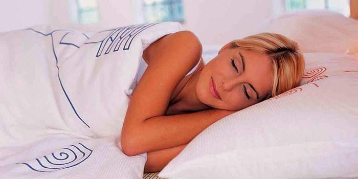 Девушка с нарощенными ресницами спит на боку