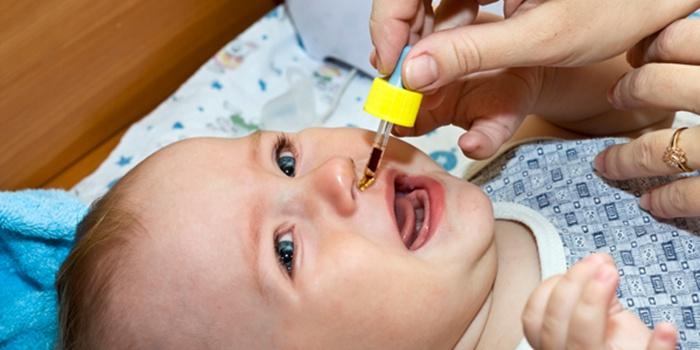 Девушка правильно чистит нос новорожденному ребенку