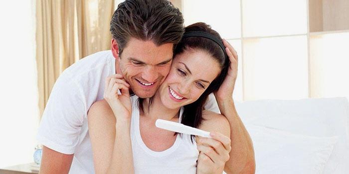 Девушка держит положительный тест на беременность