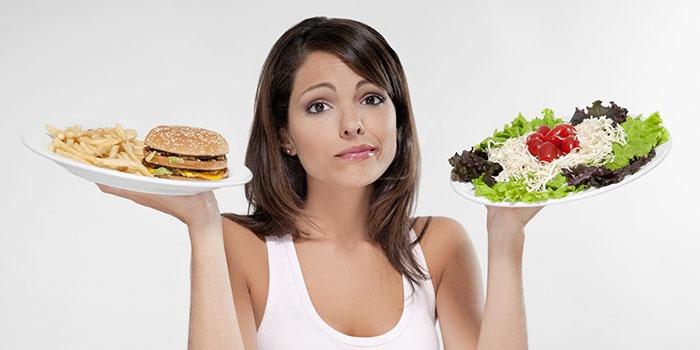 Девушка выбирает между здоровой и вредной пищей