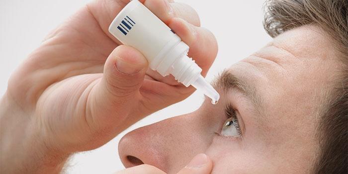 Мужчина закапывает глазные капли