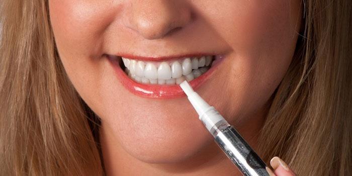 Девушка отбеливает зубы карандашом для осветления эмали