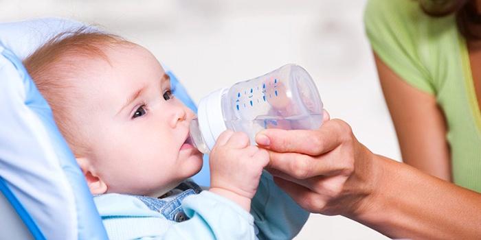 Ребенок пьет воду, чтобы оправиться после кишечной инфекции