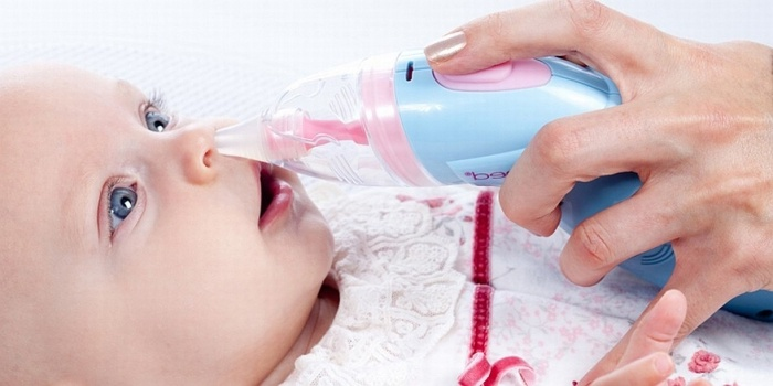 Мама чистит нос новорожденному аспиратором