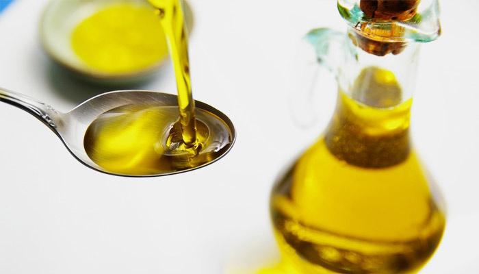 Человек наливает масло семян льна