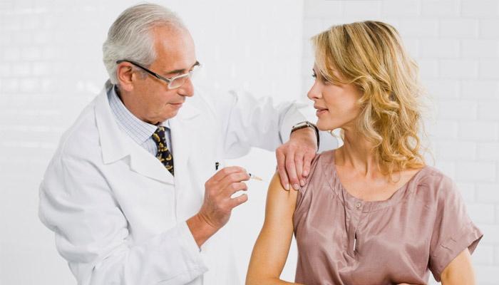 Врач делает девушке прививку АДСМ