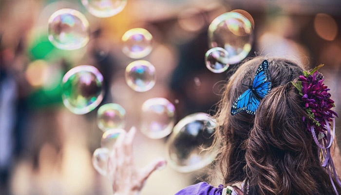 Девочка выпускает мыльные пузыри