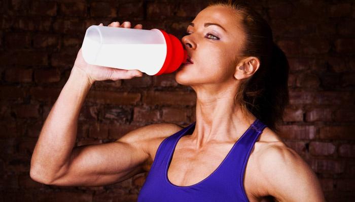 Девушка пьет протеин для набора мышечной массы