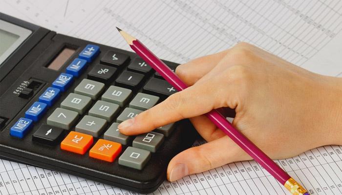 Женщина проводит расчеты на калькуляторе