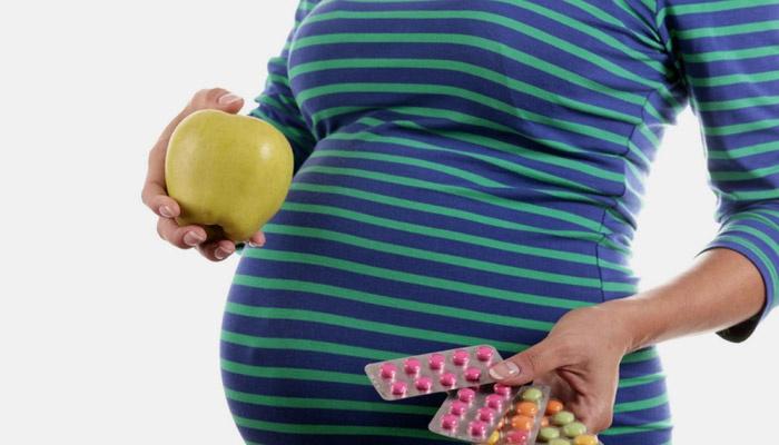 Беременная девушка держит яблоко и таблетки
