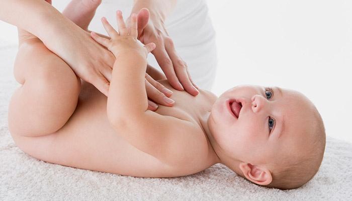 Врач ощупывает новорожденного