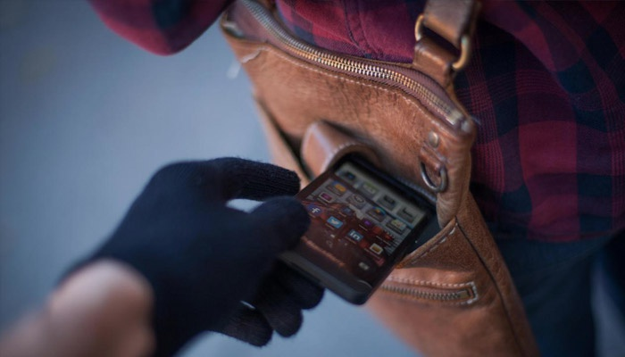 Вор вытягивает смартфон из сумки