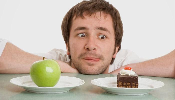 Мужчина выбирает между яблоком и тортом