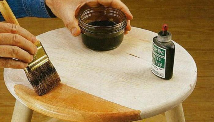Мужчина обрабатывает поверхность стула