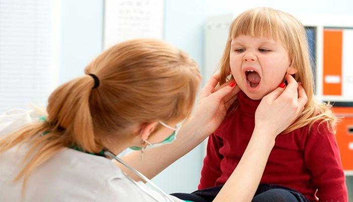 Врач осматривает лимфоузлы на шее ребенка