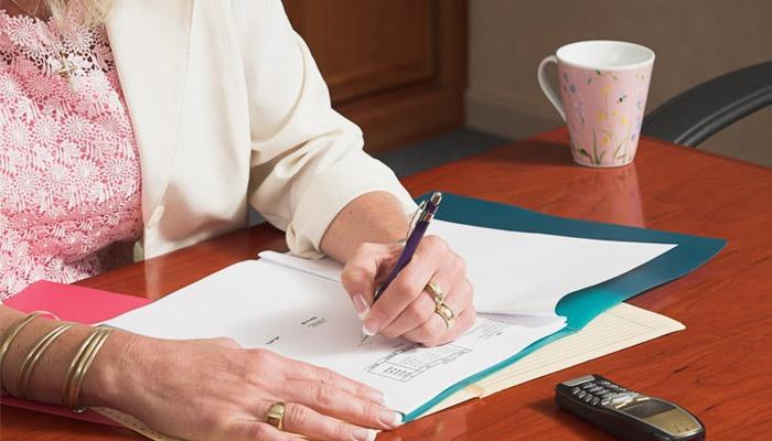 Женщина ставит подпись на документ