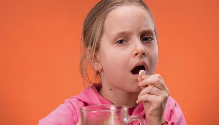 Ребенок пьет эхинацею в таблетках