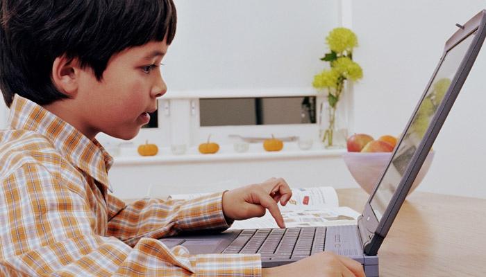 Маленький мальчик сидит за ноутбуком