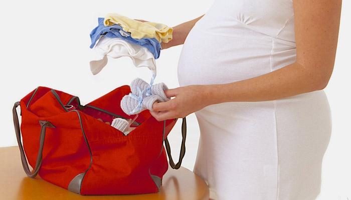 Девушка собирает вещи в роддом