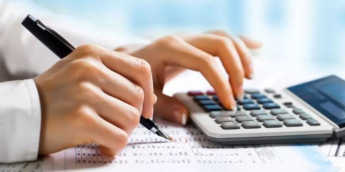 Девушка делает подсчеты на калькуляторе