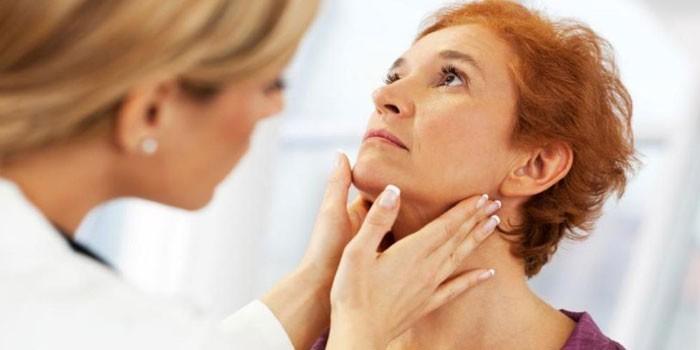 Врач осматривает лимфоузлы и щитовидную железу женщины