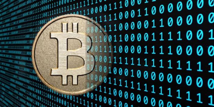 Монета со значком биткоина и компьютерный код
