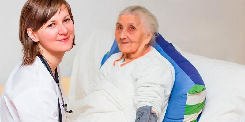 Пожилая женщина и медработник в больничной палате