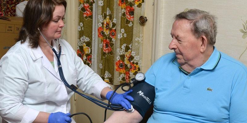 Медсестра измеряет давление пожилому человеку