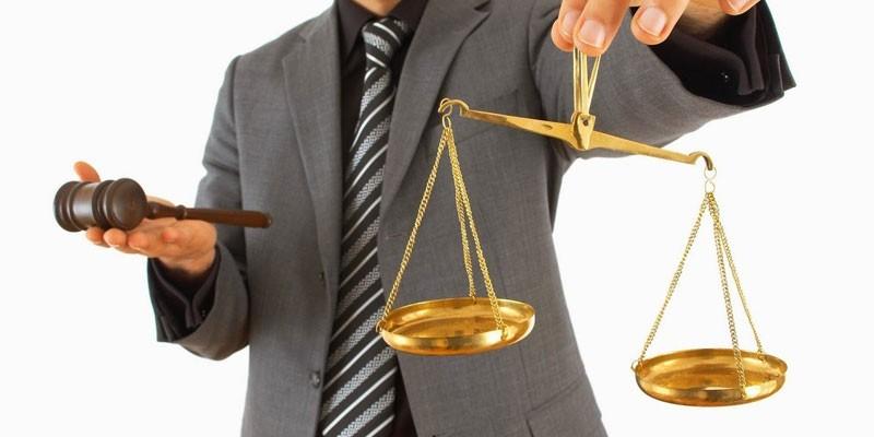 Судейский молоток и весы в руках у мужчины