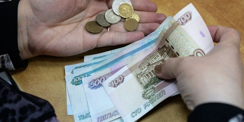 Монеты и купюры в руках у человека