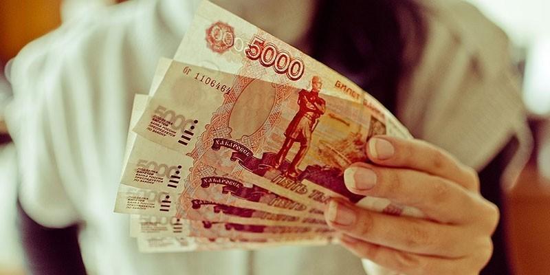 Девушка держит денежные купюры в руке