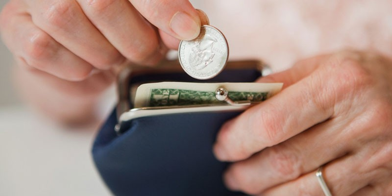 Человек кладет монету в кошелек