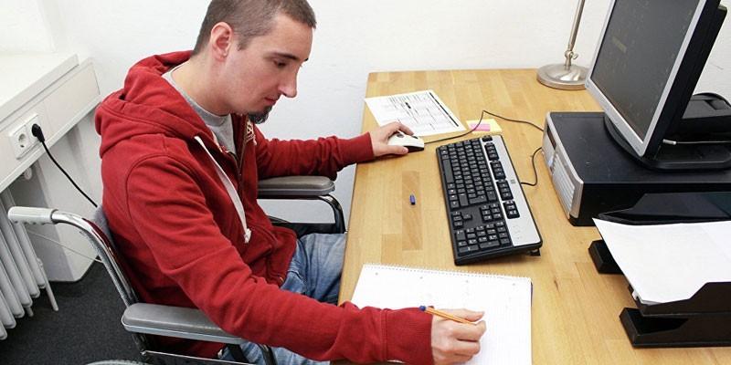 Мужчина-инвалид работает за компьютером
