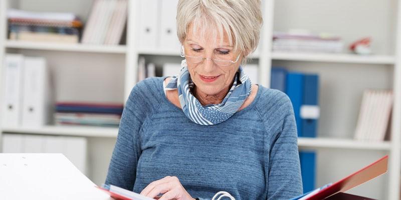 Пожилая женщина работает с документами