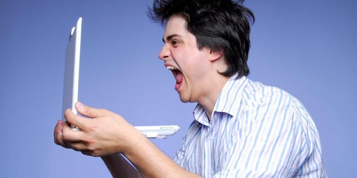 Парень кричит в ноутбук