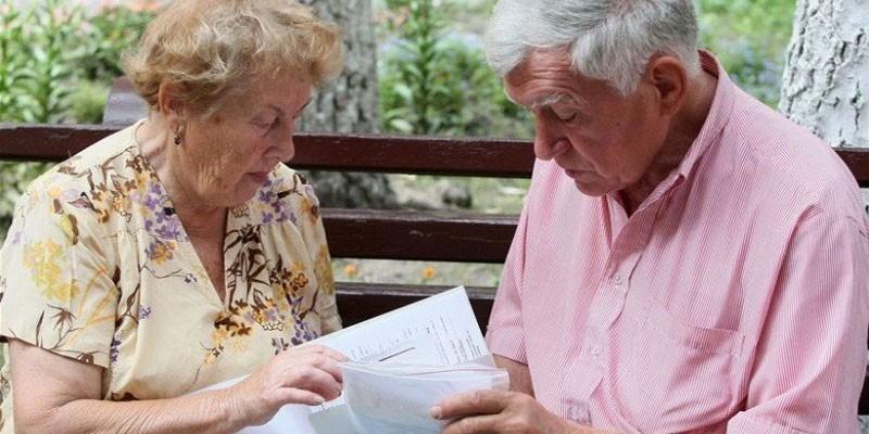 Пожилые люди изучают счета