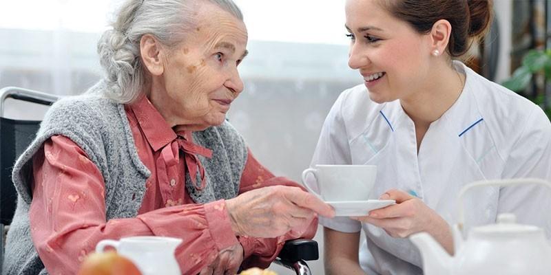 Пожилая женщина и медсестра пьют чай