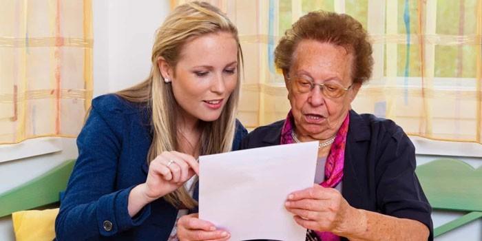 Девушка и пожилая женщина изучают документ