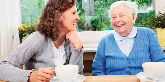 Девушка и пожилая женщина пьют чай