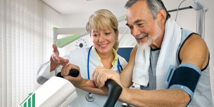 Пожилой человек на кардиотренажере и медик