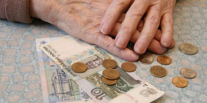 Руки пожилой женщины и деньги