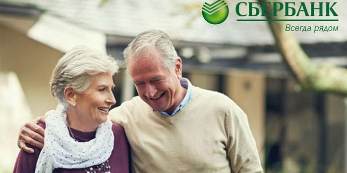 Пожилая пара и логотип Сбербанка