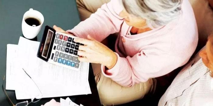 Женщина ведет подсчеты на калькуляторе