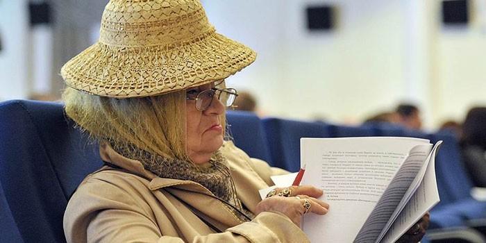 Пожилая женщина изучает документы
