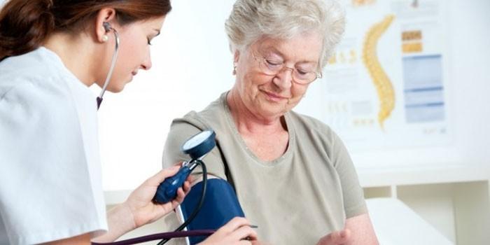 Медработник измеряет давление пациентке