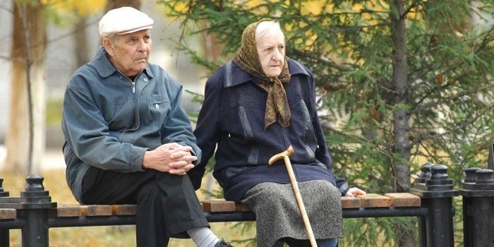 Пожилые люди сидят на скамейке